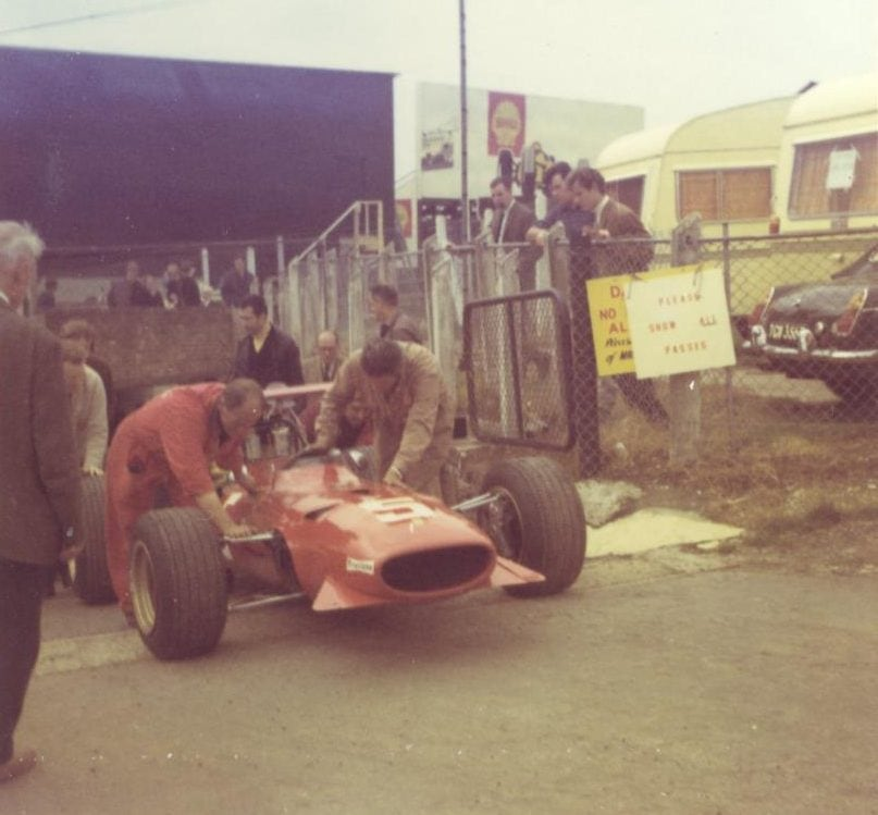 Chris Amon's Ferrrari is pushed back to the paddock after the 1968 Grand Prix. It all looked a bit rustic then!